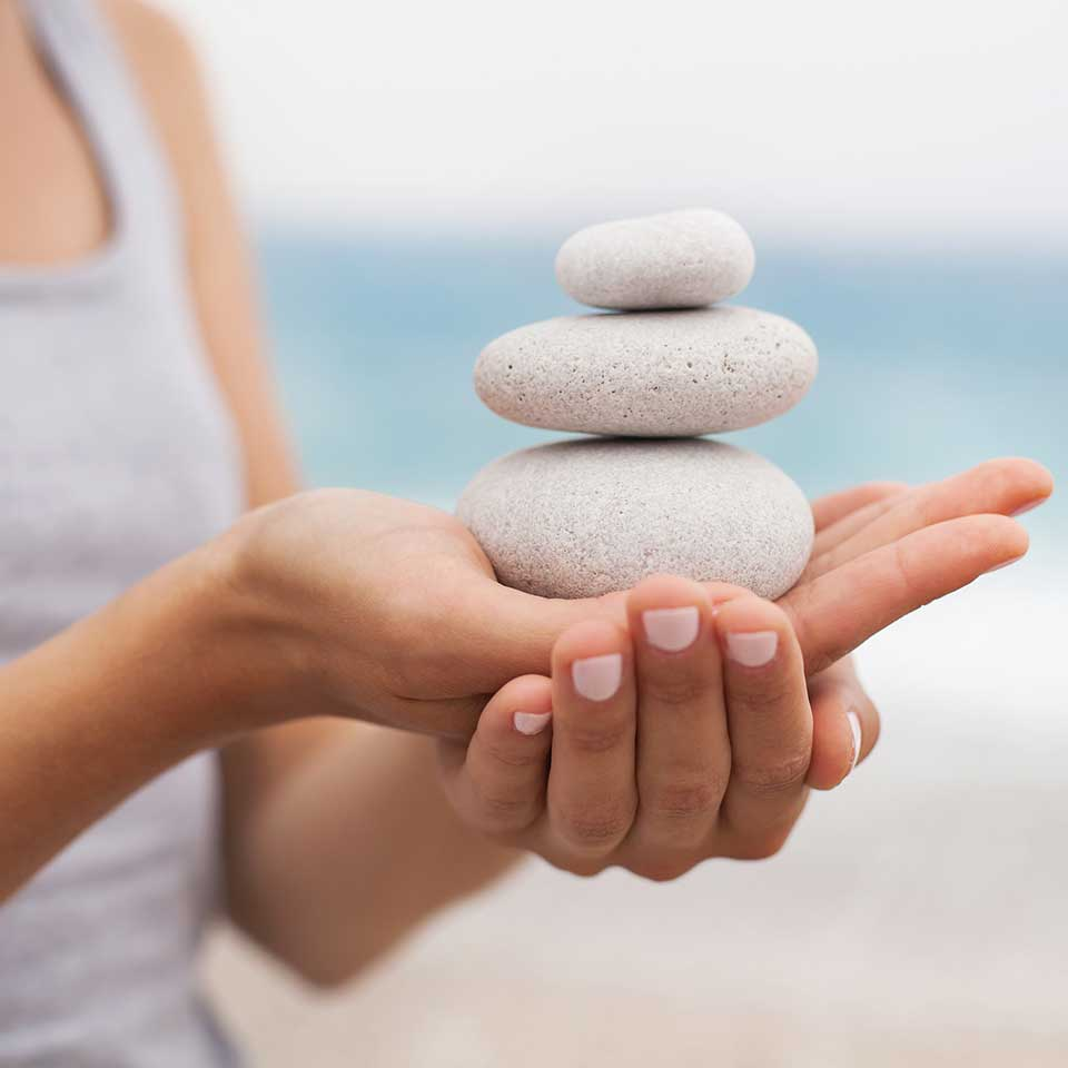 Image of balancing rocks in hands for holistic health at nuritionbliss.com